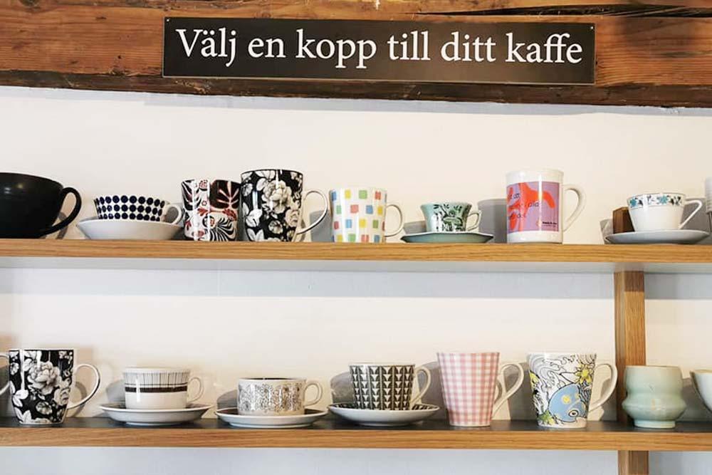 Olika kaffekoppar på en hylla med en skylt som säger: Välj en kopp till ditt kaffe.