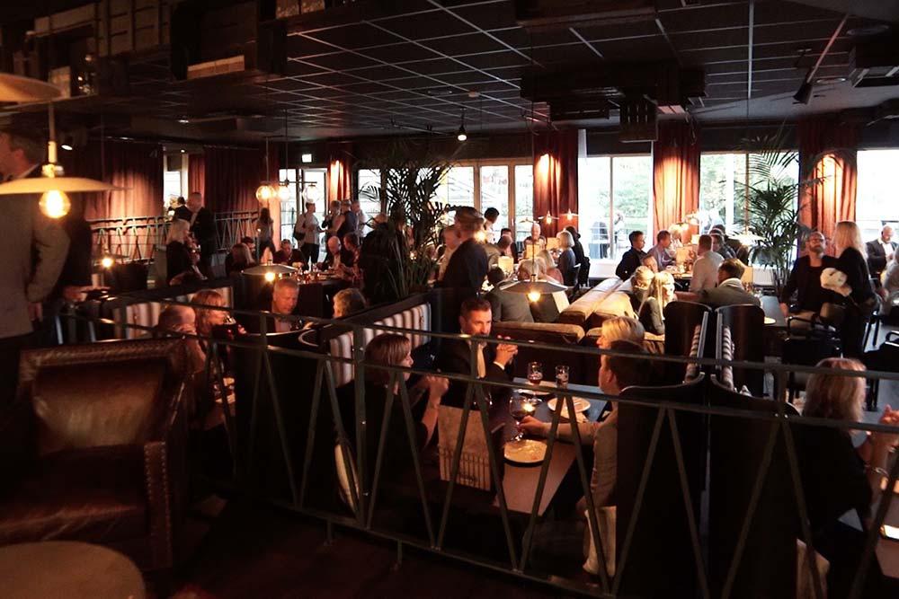 Gemytlig stämning i svagt upplyst restaurnaglokal där folk sitter och äter.