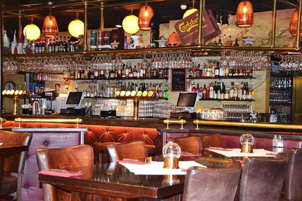 Interiör på restaurangen med ett bord och skinnstolar i förgrunden, baren i bakgrunden.