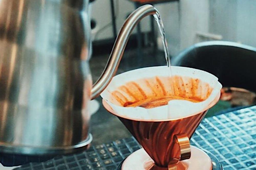 Varmt vatten hälls ur kanna ner i kaffetratt.