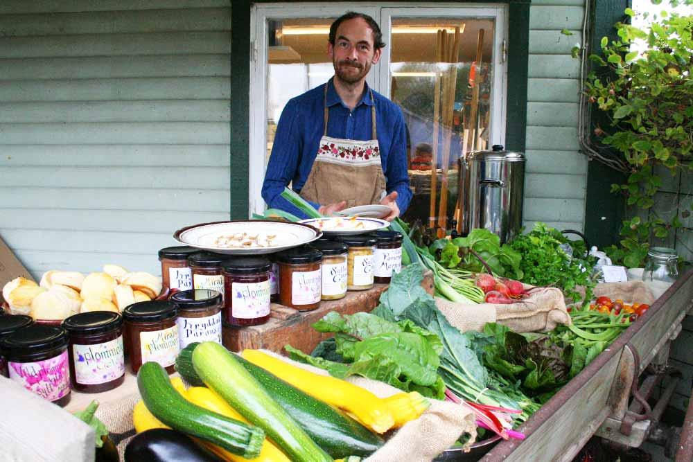George står bakom disken med grönsaker och marmelader.