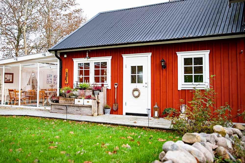 Rött hus med inglasat uterum, i förgrunden gräsmatta och en gärdesgård.