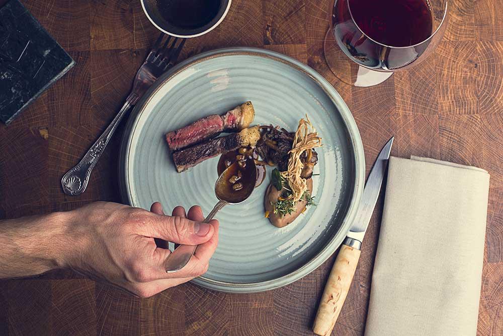 En hand lägger upp mat på en tallrik, sett ovanifrån.