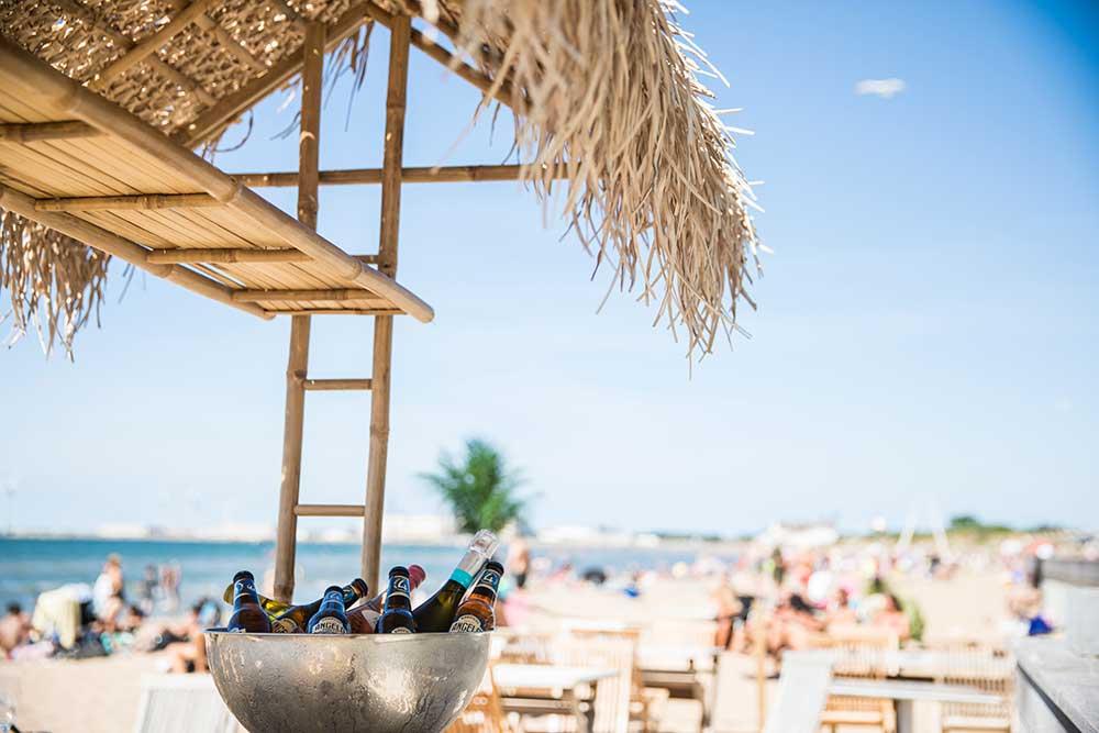 Öl i skål på kylning, i bakgrunden folk på sandstrand.