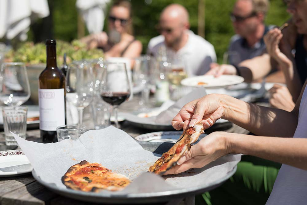 Sällskap äter pizza på uteserveringen.