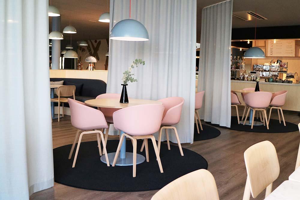 Interiör i restaurangen med runda bord och rosa stolar.