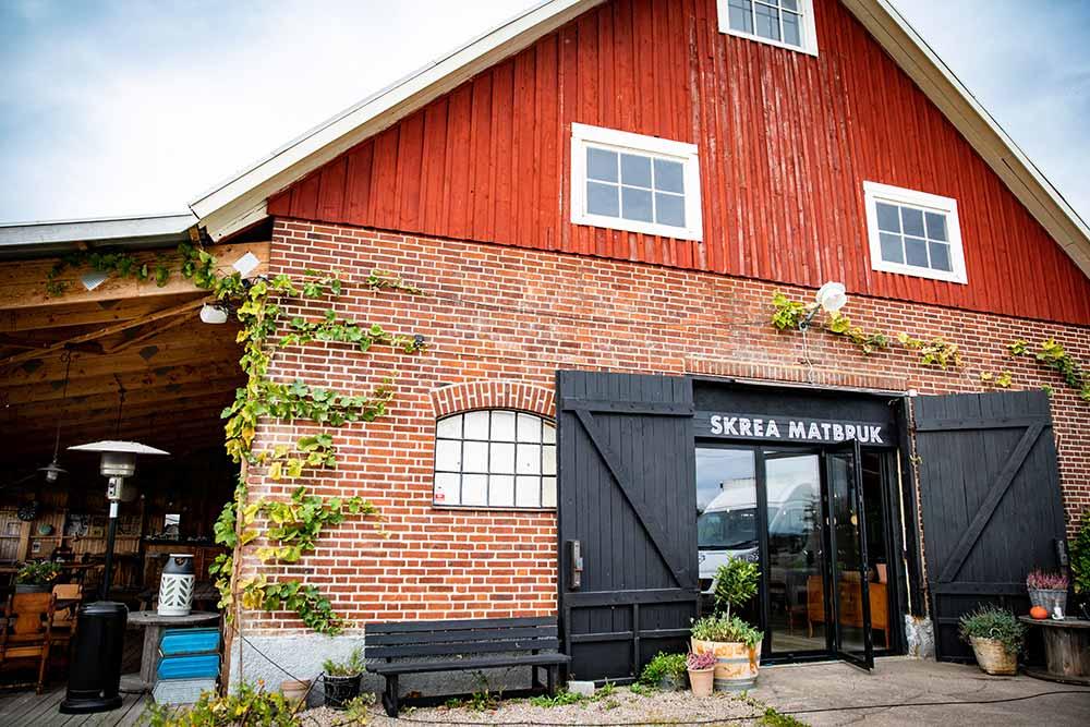 Fasaden och entrén till Skrea Matbruk, tegelbyggnad med rött trä och svarta portar.