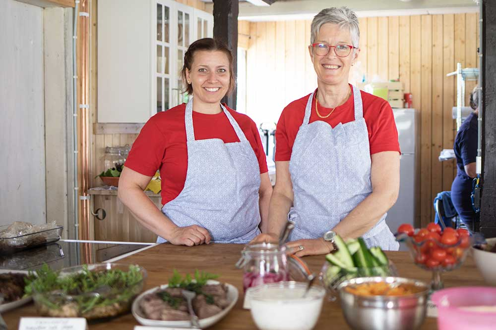 Två kvinnor med förkläden står framför serveringsfat.