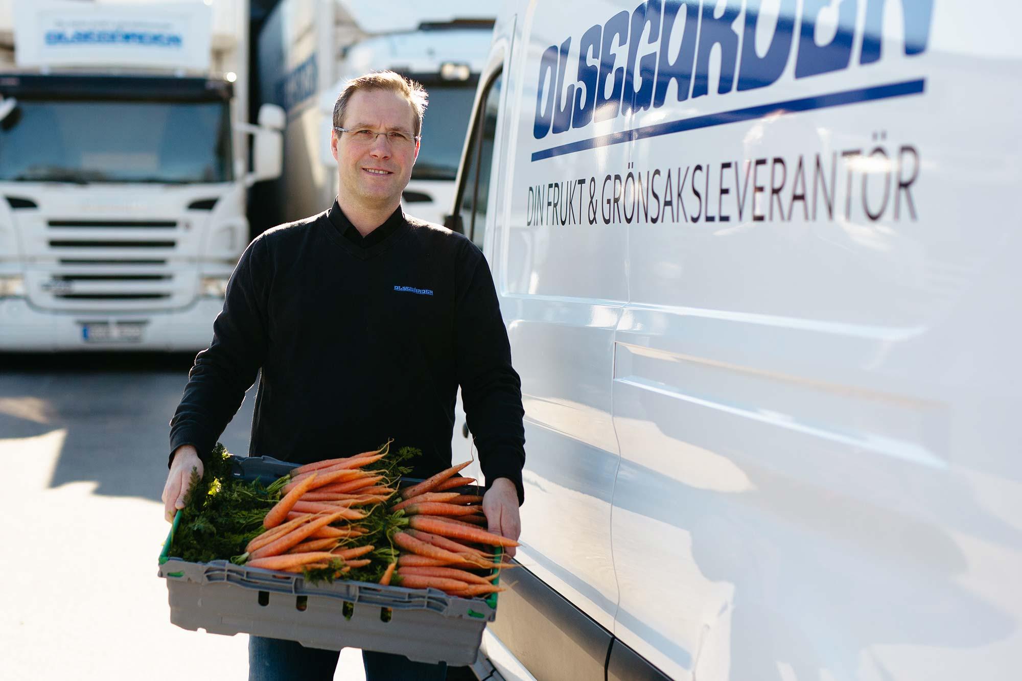 Niklas Svenmyr står med en låda morötter.