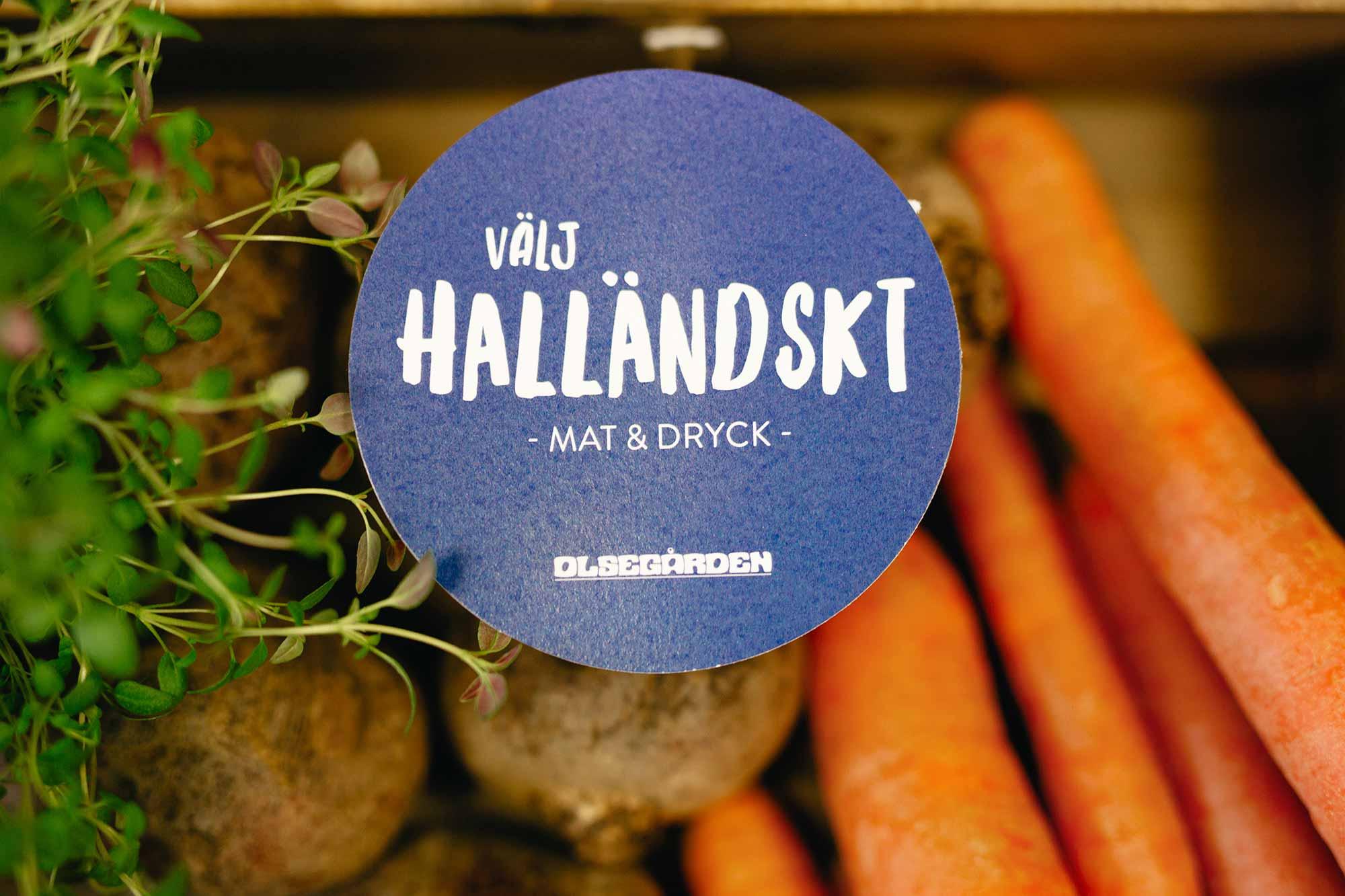 En skyltdekal, rund och blå med texten: Välj Halländskt.