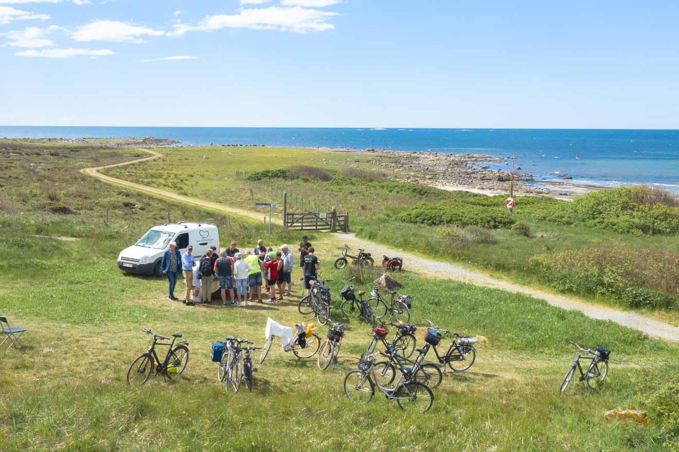 Flygbild över kusten med ett sällskap cyklister som stannat för ett stopp.