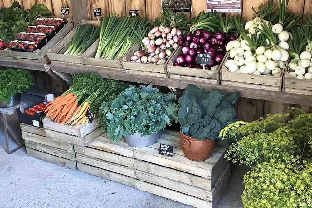 Gårdsbutik med grönsaker i trälådor.